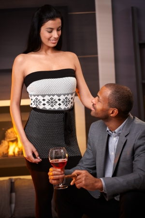Diverse couple in living room by fireplace, smiling.