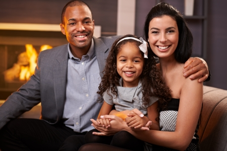 race relations: Portrait of beautiful mixed race family at home by fireplace, all smiling, little girl in the middle.