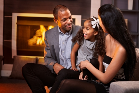 Happy ethnic family of three in living room by fireplace. photo