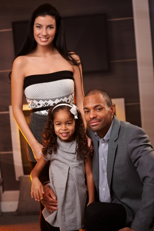race relations: Young mixed race couple and little daughter smiling at home. Stock Photo
