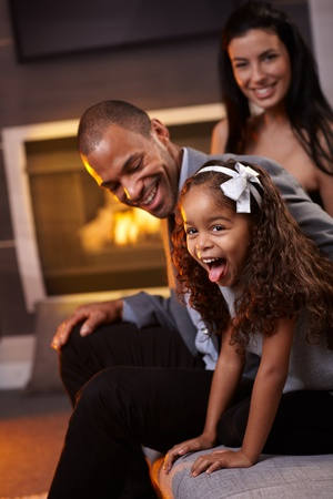 Beautiful diverse family having fun at home, little daughter sticking tongue, smiling. photo