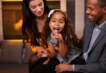 Attractive interracial family having fun at home, little girl sticking tongue. photo