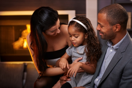 interracial relationships: Beautiful loving family sitting in living room by fireplace, smiling. Stock Photo