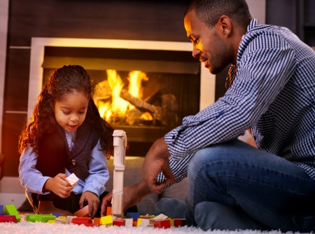 Afro father and little daughter playing together in living room floor by fireplace. Stock Photo - 14427900