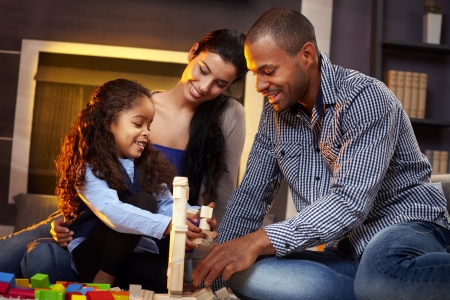 Happy interracial family of three playing together at home on floor, building tower by cubes. photo