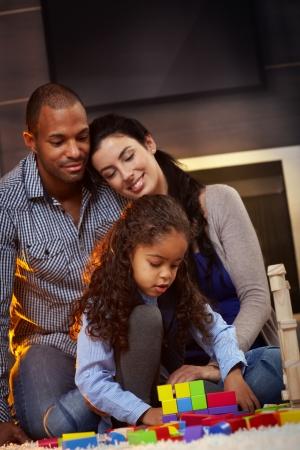 interracial marriage: Happy family razza mista seduta sul pavimento di casa, il padre e la madre a guardare bambina giocare, sorridente.