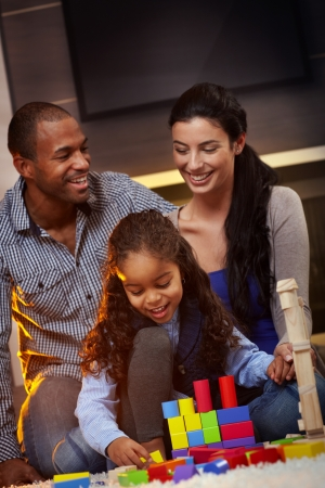 Happy interracial family sitting on floor at home, playing together, smiling. photo