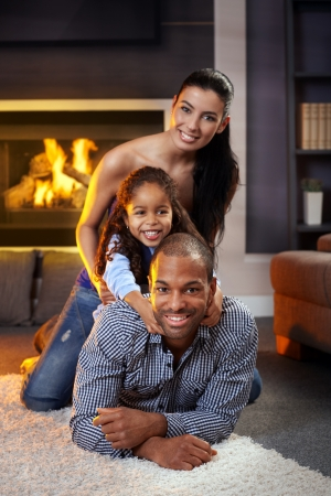 fireplace family: Portrait of happy diverse family at home lying on each other, smiling. Stock Photo