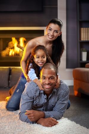 interracial marriage: Ritratto di famiglia felice a casa sdraiato diversi gli uni sugli altri, sorridente.