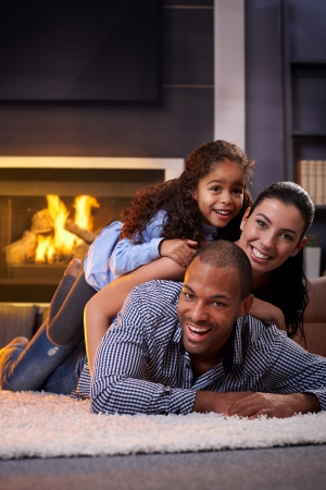 Happy interracial family having fun at home by fireplace, lying on each other's back, laughing. photo