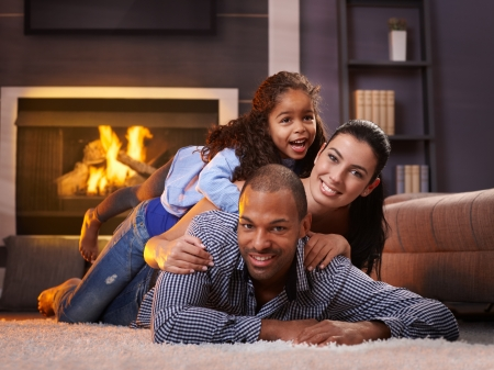 fireplace family: Beautiful mixed race family having fun at home, laughing.