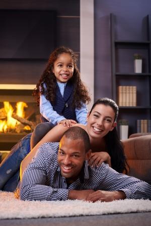 interracial marriage: Happy family diverse divertirsi in casa sul pavimento, sdraiata a vicenda.
