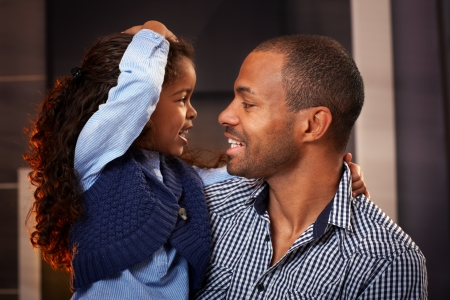 Happy black father and cute little daughter embracing, smiling. photo