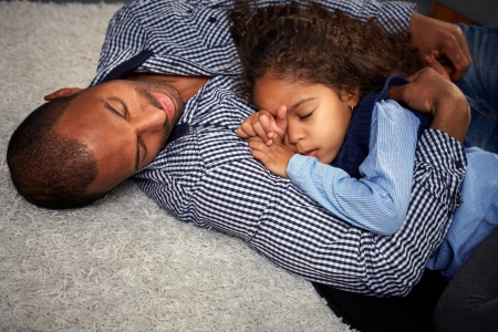 Ethnic father and beautiful little daughter sleeping on floor at home photo