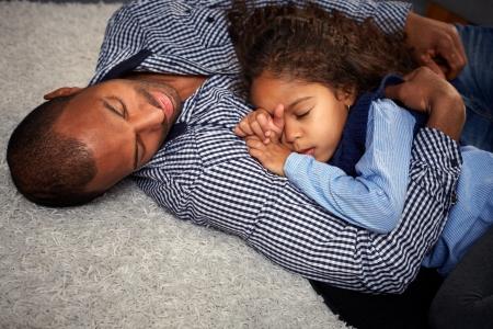 enfant qui dort: Père ethnique et belle petite fille dort sur le plancher à la maison