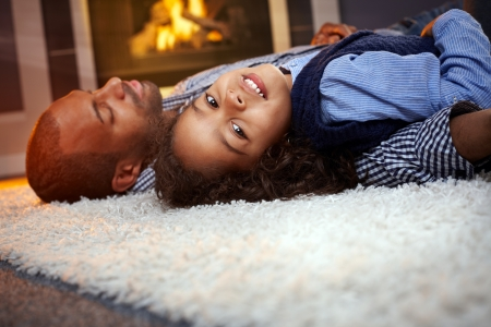 Little ethnic girl and father lying on floor at home, father sleeping. photo