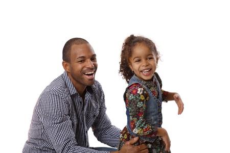 Padre feliz étnica y su pequeña hija linda riendo, divirtiéndose, el padre de ponerse en cuclillas.