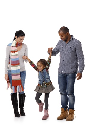 Happy interracial family with little girl walking, jumping, having fun. photo