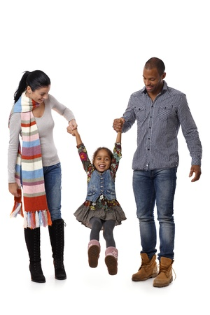 Mixed race family walking, father and mother swinging little daughter between them. Stock Photo