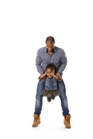 Afro father swinging little daughter between legs, little girl laughing. Stock Photo - 14427332