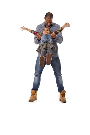 Ethnic father swinging little daughter between legs, playing, having fun, laughing. Stock Photo - 14427330