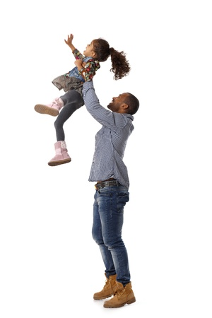 Ethnic father throwing little daughter in the air, having fun, laughing. photo