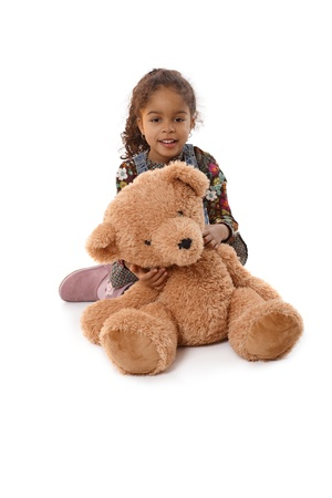 Beautiful ethnic little girl hugging a huge plush bear, smiling. Stock Photo - 14427352