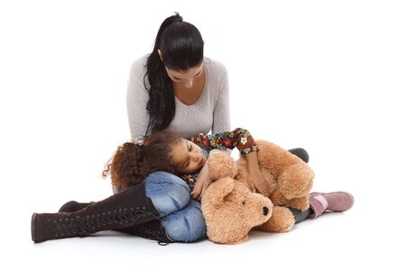 Little daughter lying in mothers lap, hugging huge plush bear. photo