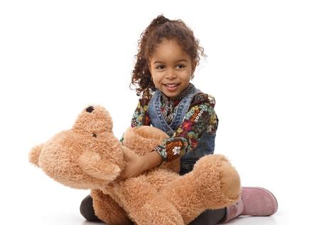 Cute ethnic little girl holding huge plush bear, playing, smiling.