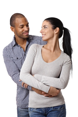 interracial relationships: Diverse loving couple holding hands, embracing, smiling at each other.