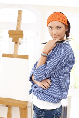 creativity artist: Attractive painter woman posing with brush in hand. Stock Photo