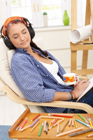 Artist girl enjoying relaxation, smiling with eyes closed, headphones on, drinking coffee, colorful pencil drawing. photo