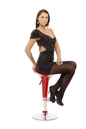 Pretty woman in sexy black mini dress and high heels sitting on barstool, isolated on white. photo