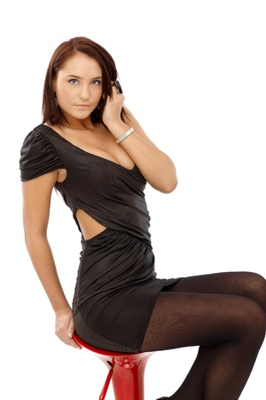 Sexy woman posing on barstool, in elegant black mini dress, looking at camera. photo