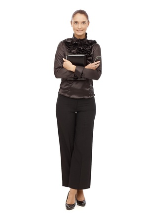 Smiling businesswoman in black holding personal organizer and phone, arms and legs crossed, cutout on white. photo