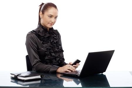 Elegant businesswoman sitting at desk working on laptop computer, holding mobile phone. photo