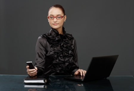 Businesswoman in black fancy shirt, red glasses, texting on mobile phone, using laptop computer. photo
