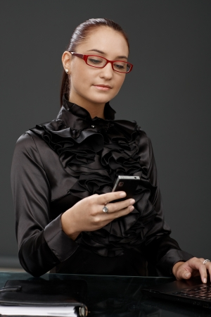 Smiling elegant businesswoman texting on mobile phone, smart shirt and red glasses, using laptop. photo
