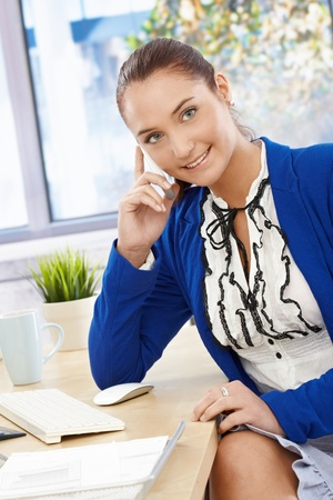 Pretty office assistant girl sitting at desk speaking on mobile phone, smiling happily. Stock Photo - 14746501