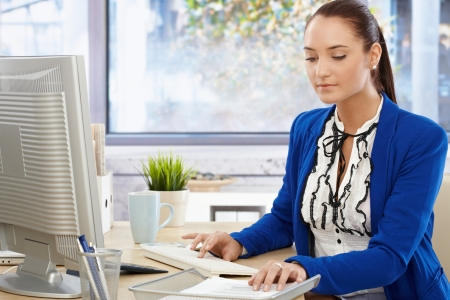 white color worker: beautiful office girl busy working at bright desk, typing on keyboard and checking document, looking down.