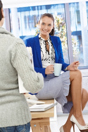 Attractive office girl enjoying coffee break chatting to coworker, sitting on desk with coffee mug handheld. photo