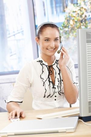 callcenter: Happy callcenter operator girl at desk, using headset, working with desktop computer, smiling.