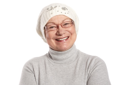 Portrait of happy elderly lady smiling in cap and polo-neck sweater. photo