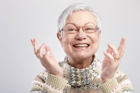 Closeup portrait of happy old woman gesturing by hands. photo