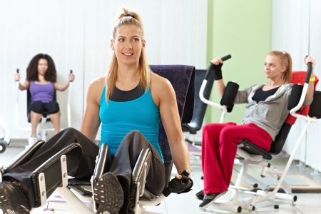 weight machine: Young women exercising on weight machine at the gym.