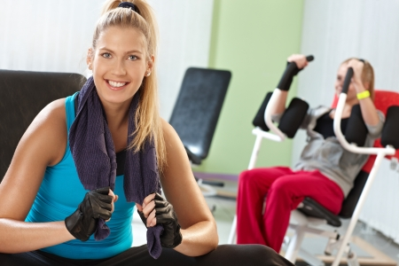 Happy attractive girl resting at the gym, smiling, sitting on exercise machine. photo