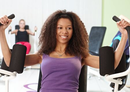 weight machine: Pretty ethnic girl exercising at the gym on weight machine, smiling. Stock Photo