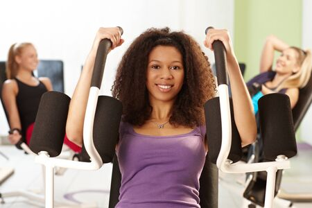 Pretty ethnic girl doing arm exercises at the gym on exercise machine, smiling. photo