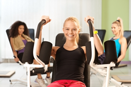 weight machine: Young girl exercising at the gym, using weight machine, smiling.