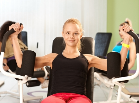 Happy blonde girl exercising at the gym on weight machine, smiling. photo